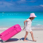 Little adorable girl with big colorful suitcase in hands walking on tropical beach
