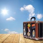 Reisekoffer auf Holz vor Himmel