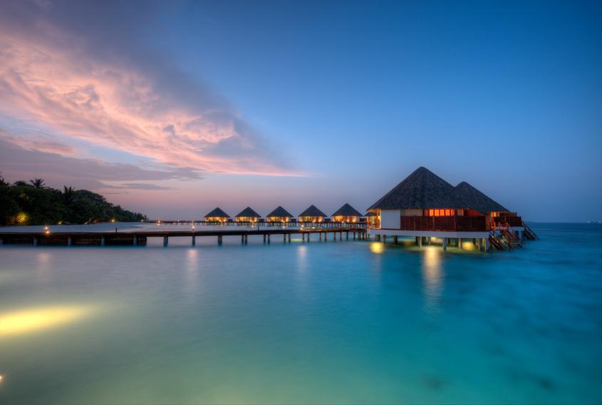 Water villas in lagon, Maldives resort island in sunset
