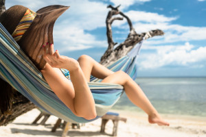 Woman on beach vacation relaxing in hammock by the sea