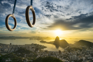 Gymnast rings hanging in golden sunrise light above Sugarloaf Mountain and the city skyline in Rio de Janeiro, Brazil
